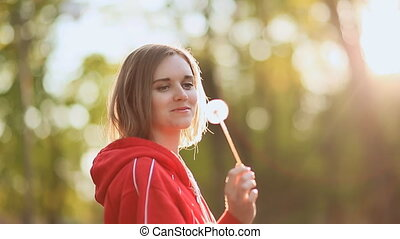 Young beautiful woman holding dandelion on meadow in evening...