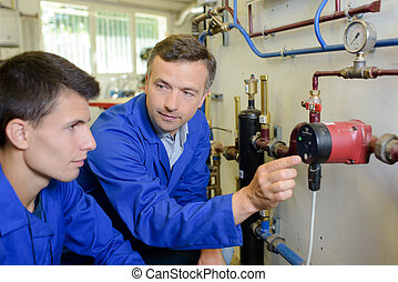 Plumber showing pipework to apprentice
