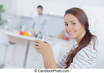 Lady drinking glass of wine, man cooking