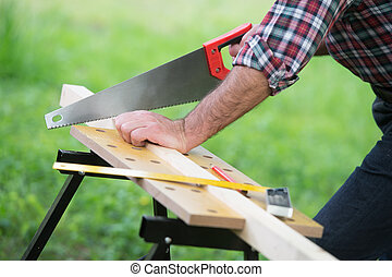Carpenter sawing a wooden square with a wood saw outdoor