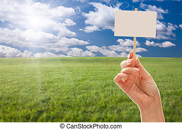 Blank Sign in Hand Over Grass Field and Sky - Blank Sign in...