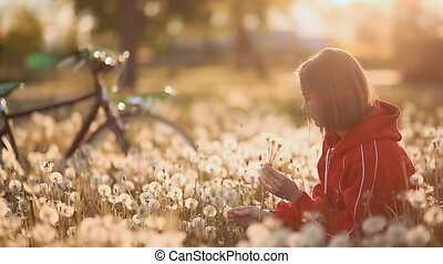 Young girl sitting in a field of dandelions. The background bicycle.