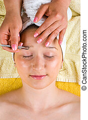 Beautician tweezing woman eyebrows in a spa center