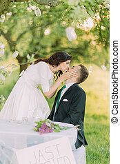Romantic picknick in park. Playful bride kissng her lovely...