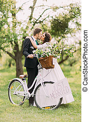Sensual young newlywed couple kissing in park with groom holding bicycle
