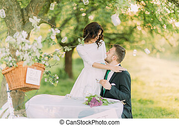 Romantic picknick in park. Playful bride hugging her lovely...