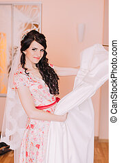 Pretty young girl holding wedding gown in dressing room,...