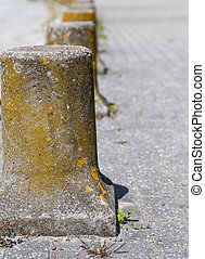 road barriers from granite with moss on side a street