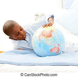 Cute little boy playing with a terrestrial globe in his...