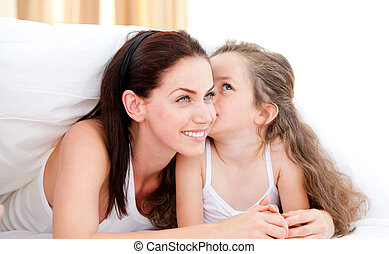 Adorable little girl kissing her mother lying on a bed
