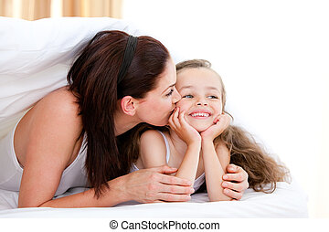 Attentive mother kissing her daughter lying on a bed