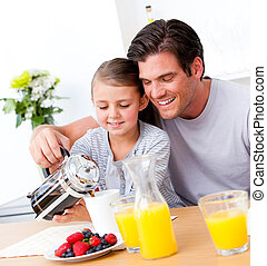 Cheerful father and his daughter having breakfast together...