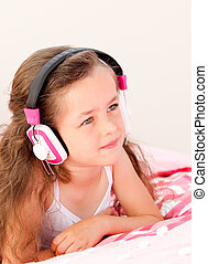 Smiling little girl listening music lying on her bed at home