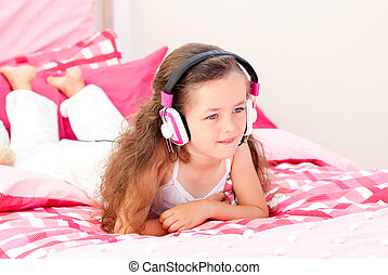 Cheerful little girl listening music lying on her bed at...