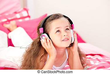 Adorable little girl listening music lying on her bed at...