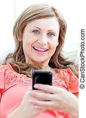 Radiant woman sending a text lying on a sofa at home