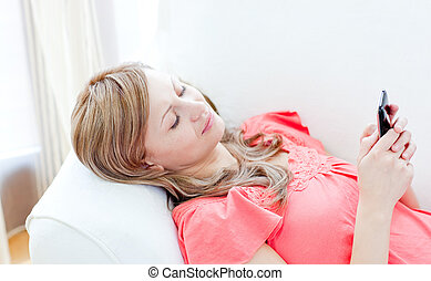 Attractive woman sending a text lying on a sofa at home