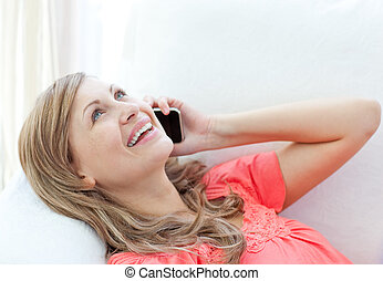 Jolly woman talking on phone lying on a sofa