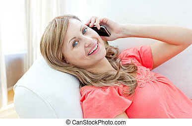 Happy woman talking on phone lying on a sofa
