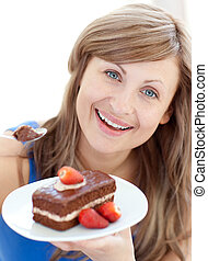 Bright woman holding a piece of chocolate cake