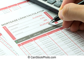 Mortgage loan balance sheet with hand hold a pen