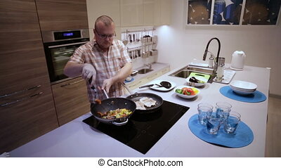 Man Prepares Vegetables and Roast Meat