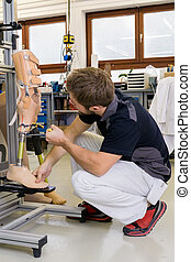 Technician working on prosthetic leg parts