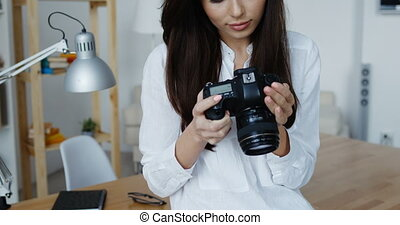 Attractive smiling brunette female photographer in white...