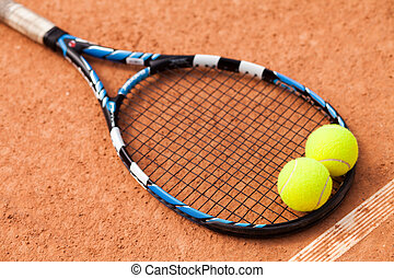 Tennis racket with two balls lying on the sandy tennis court