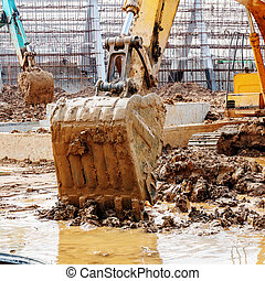 The excavator is dredging - Close-up of a construction site...