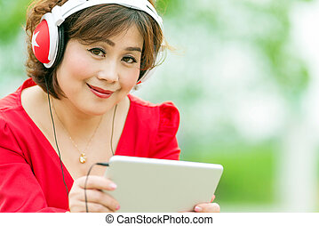 Asian woman browsing tablet - Happy woman browsing tablet...