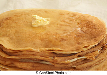 Butter on pancakes - Butter melts on a large pile of golden...