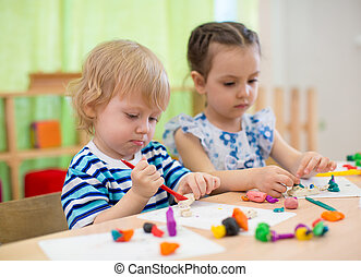 Kids or children creating arts and crafts in kindergarten -...