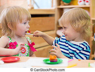 Two kids playing in kindergarten together. Boy feeding girl....