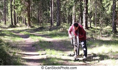 Man Repairing a Wheel of Bicycle in Forest