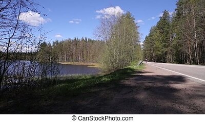 Man Riding on Bicycle by the Road near Lake