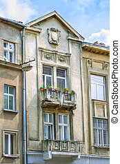 facade of the old house with a balcony on the city street -...
