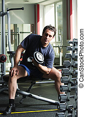 Man training biceps with dumb-bell - Man in shirt and shorts...