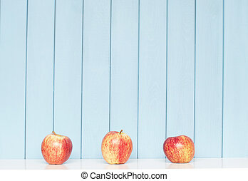Three apples - tree red apples on the shelf on blue wooden...