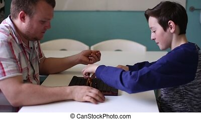 Man and Boy Playing in Board Game - Man and teen Playing in...