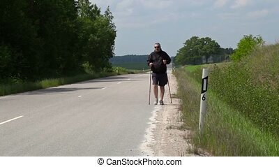 Hiker with walking sticks on the highway
