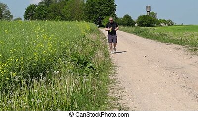 Man running along the edge of the rural road in summer
