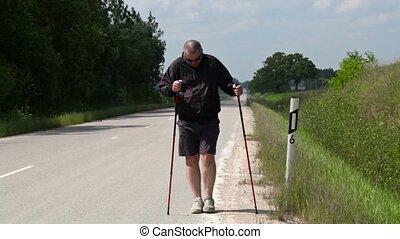Hiker with walking sticks do exercises on the highway