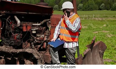 Worker talking on smart phone near broken bulldozer