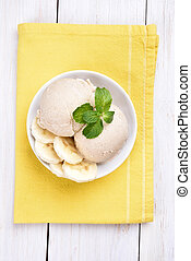 Banana ice cream in bowl, top view - Scoop of banana ice...