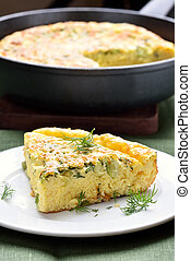 Piece of omelette with herbs, cheese and zucchini
