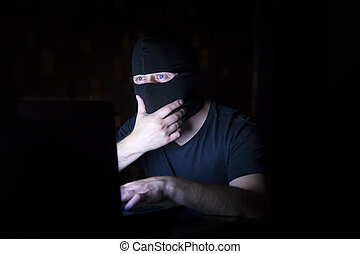 Hacker in black mask with laptop - Online man criminal in...