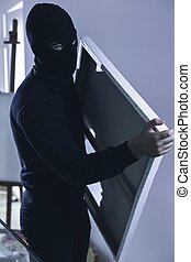 No one can stop him - Shot of a robber leaving a house with...