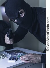 Its all his now - Shot of a masked robber pointing a gun at...