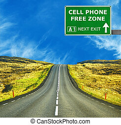 CELL PHONE FREE ZONE road sign against clear blue sky